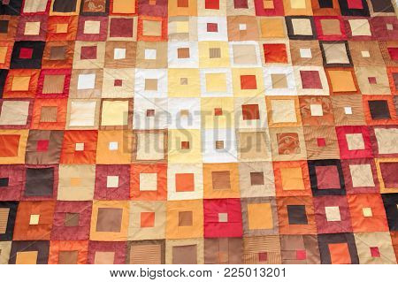 backdrop, decoration, interior design concept. there is adorable background created with quilt sewed of pieces of marvelous fabrics invarious colors and shades