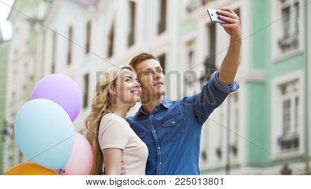 Girlfriend and boyfriend hugging in street and taking selfie, romantic photos, stock video