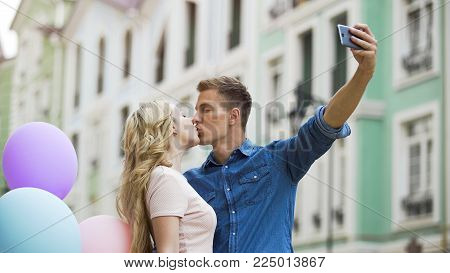 Sweethearts kissing in front of smartphone camera taking romantic selfie on date, stock video