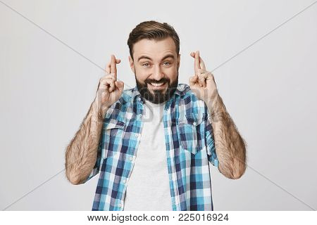 Indoor shot of excited bearded guy showing wish gesture by crossing fingers on both hands, smiling and lifting eyebrows, over gray background. Man hopes that today he will receive paycheck.
