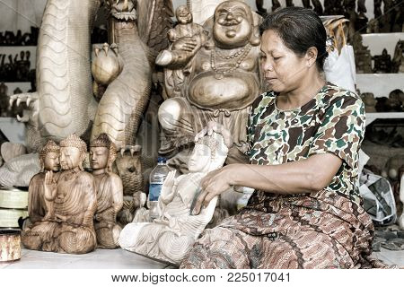 A woman is polishing wooden Buddha. Bali. Ubud. Indonesia