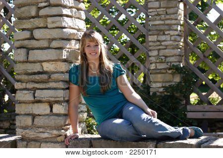 Pretty Teen Girl Sitting On A Wall
