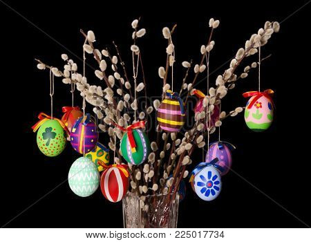 Colored easter eggs on willow bouquet with pussy willows. Religious decoration. Paschal eggs on branches with furry catkins in crystal vase. Salix. Front view, horizontal, on black background. Photo.