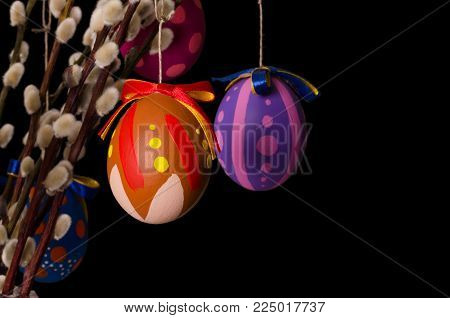 Two colored easter eggs on willow bouquet with pussy willows. Religious decoration. Paschal eggs on branches with furry catkins in glass vase. Salix. Front view, horizontal, on black background. Photo