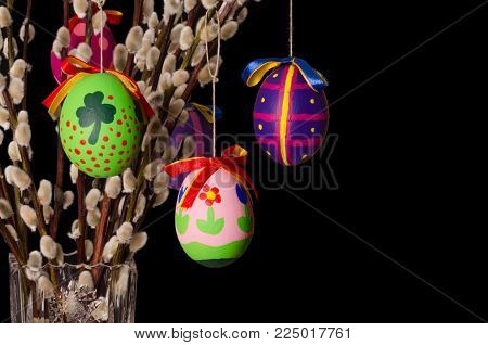 Easter eggs on willow bouquet with pussy willows. Religious decoration. Colored Paschal eggs on branches with furry catkins in crystal vase. Salix. Front view, horizontal, on black background. Photo.