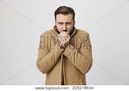 Close up portrait of mature male who feels very cold outside over white background. Man hopes that he will not get cold. Who knew that this day is bad for a date outside. Emotions concept
