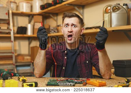 Multimeter for electrician. Crazy aggressive batty mad fun young man in plaid shirt, digital electronic engineer repairing, soldering computer PC motherboard in workshop at wooden table with tools poster