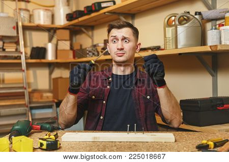 Pretty fun gaga zonked caucasian young man in plaid shirt, black T-shirt, gloves twisting by screwdriver screw, working in carpentry workshop at wooden table place with piece of wood, different tools