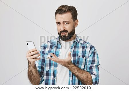 Portrait of unsatisfied man holding smartphone and gesturing with another hand, expressing dislike and disappointment while looking at camera, standing over gray background. Advertisement concept