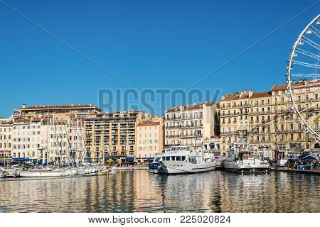 Marseille, France - December 4, 2016: Sunday ambiance at the Old Vieux Port in Marseille, France. It is a busy port, used as a marina and as a terminal for boat trips, and hosts a fish market. Ferris wheel in the frame field.