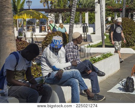 Spain, Canary islands, Tenerife, Puerto de la cruz, December 23, 2017, three african men sitting on flower bed, street sellers of handbags and backpack, palm tree garden and walking tourist