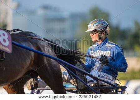 STOCKHOLM, SWEDEN - AUGUST 5, 2015: Harness race driver Björn Goop preparing a horse for a race. Björn Goop won Prix d'Amerique 2018 considered to be the biggest race in the world.