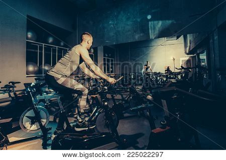 The Guy Is Engaged In A Bicycle Simulator In The Gym. Toned Image.