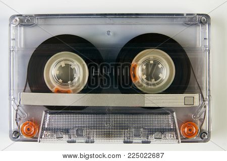 Old compact audio cassette. Vintage cassette tape isolated white background, close-up top view. Cassetes year 1980