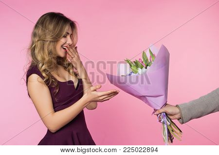 A man is giving a beautiful tulip bouquet  to his girlfriend. Lady is happy and amazed. Happy woman's day
