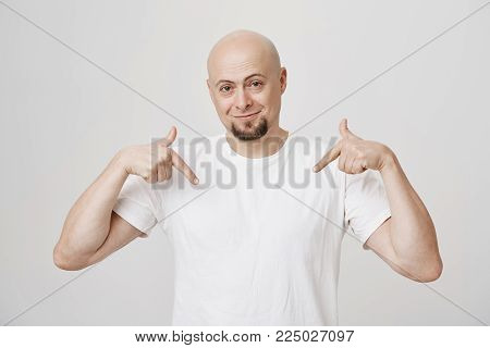 Indoor shot of confident and satisfied bald bearded man pointing with index fingers at his white t-shirt and smiling, standing against gray background. Guy directs down to show his new sneakers.