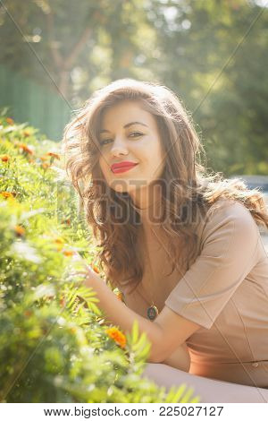 portrait of smiling woman poses on background bed of flowers