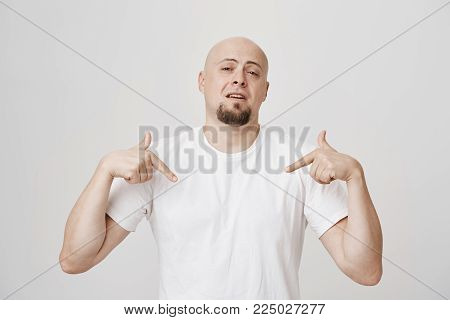 Portrait of smug and confident bald caucasian man pointing down while wearing white t-shirt and standing over gray background. Guy assures woman that he will show her heaven once they reach bedroom.