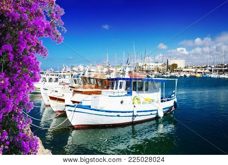 colorful fishing boats near old fortress, Heraklion port, Crete, Greece with flowers