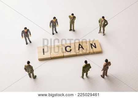 Miniature figures businessman : meeting on i can word by wooden block letters on white paper background, in concept of business and corporation