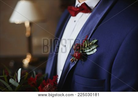 Stylish groom in blue suit with red bowtie and green-red boutonniere on his jacket - wedding details.