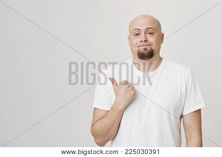 Indoor portrait of disappointed and gloomy bald male model with beard pointing indifferent left with thumb, standing over gray background. Man directs at bedroom where his wife still change clothes.