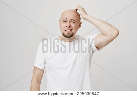 Portrait of confused bald caucasian male model with stupid expression, scratching head and looking aside not having any clue, standing over gray background. Man forgot something but do not know what.