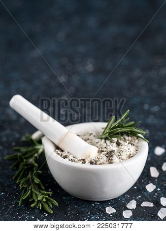 Close up view of mortar and pestle with sea salt scented rosemary and lemon zest. Sea salt scented herb rosemary on dark blue background. Scented salt and ingerdients. Copy space