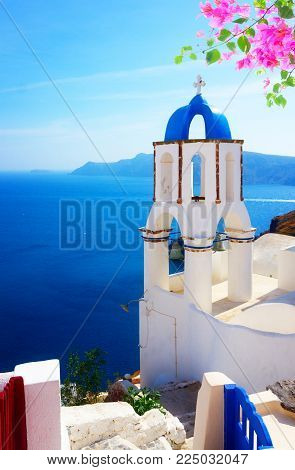 view of caldera with blue sea and belfry, Oia, Santorini with flowers