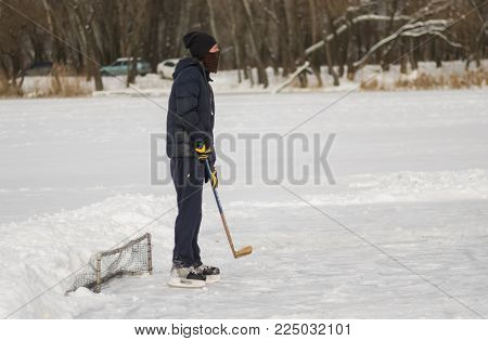 Dnipro, Ukraine - January 27, 2018: Amateur man playing hockey as a goalkeeper standing against tiny gates on a frozen river Dnepr in Ukraine
