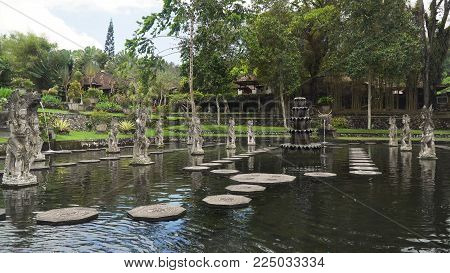 Hindu Balinese Water Palace Tirta Gangga with statues of the gods, fountains on Bali island, Indonesia. Tirta Gangga the former royal water palace is a maze of pools and fountains surrounded by a lush garden and stone carvings and statues.