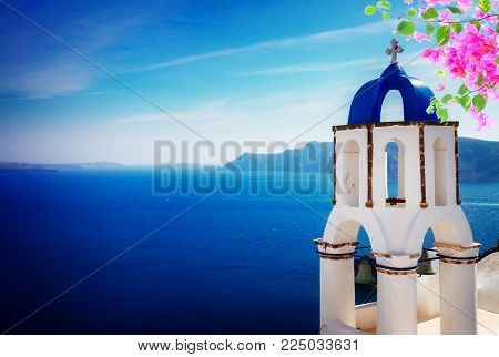 view of caldera with blue belfry, Oia, Santorini with flowers
