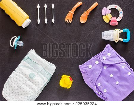 Baby set of cloth diaper, disposable diaper, baby powder, tither, cotton buds, spoons, soother, nibbler and rubber duckling on dark background with copy space. Top view or flat lay