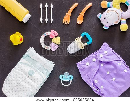 Baby set of cloth diaper, disposable diaper, baby powder, tither, cotton buds, spoons, soother, nibbler, rubber duckling and toy on dark background. Top view or flat lay