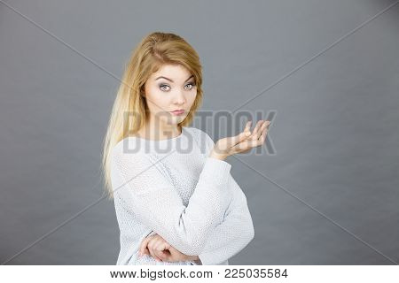 Confused young blonde woman looking annoyed. Confusion face expressions concept. Studio shot on grey background.