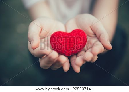 Sharing Love and Heart red color on women hand in valentine's day vintage color tone