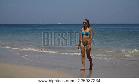 Young girl in bikini comes out from the sea after swimming. Girl in bikini enjoy nature sea paradise summer vacation.
