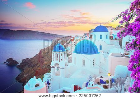 vew of Oia, traditional greek village of Santorini, with blue domes of churches at sunset, Greece with flowers
