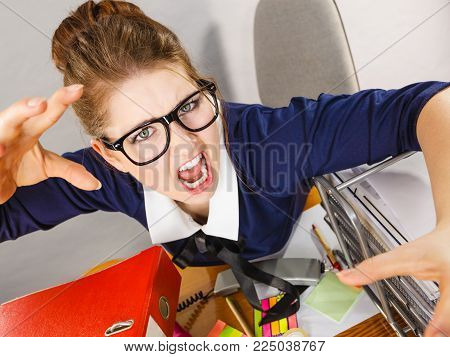 Mobbing at work, bad job relations concept. Angry mad bossy businesswoman being furious sitting working at desk full off documents in binders.