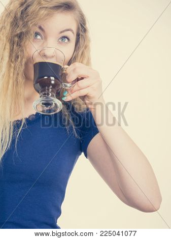 Positive woman holding black coffee about to drink. Getting morning energy, hurry up before going to work.