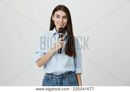 Attractive stylish woman talking in microphone expressing happiness and joy while standing over gray background. Host of wedding ceremony congratulate newlyweds and entertain guests.