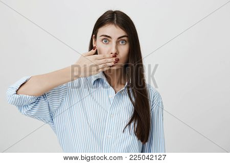 Indoor shot of young stylish woman covering her mouth with hand, looking anxious with lifted eyebrows, standing over gray background. Trendy woman with stylish manicure promises to keep mouth shut.