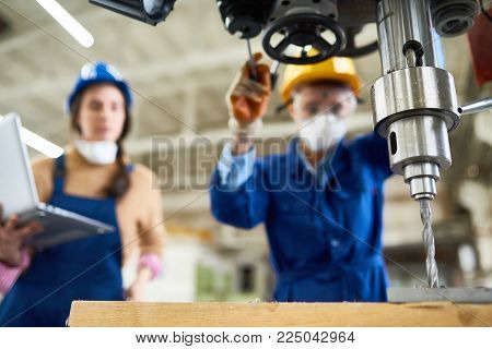 Portrait of two female factory workers operating boring mill at modern industrial plant, focus on foreground, copy space