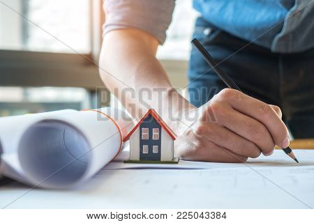 Home design concept,Architects are writing home plan,The model house place on House plan,House plan rolls side by side.
