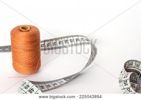 Accessories for sewing: thread and centimetre on a white background. Brown bobbin thread.