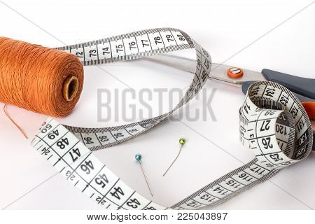 Accessories for sewing: thread, scissors, needle and centimetre on a white background. Brown bobbin thread.
