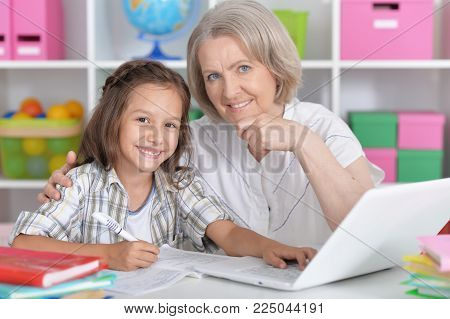 granny with her granddaughter using laptop at home