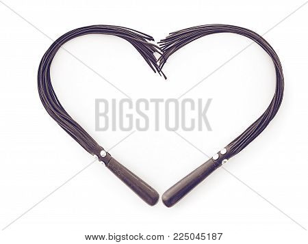 The figure of the heart is made of two leather whips for sex games. The idea for a Valentine's day background (applicable for sex shops, original cards or unusual congratulations)
