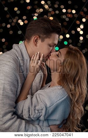 Couple intimate moment, hugging while smiling, ready to kiss with closed eyes on background with lights. Beautiful woman touching her partners face. Low light