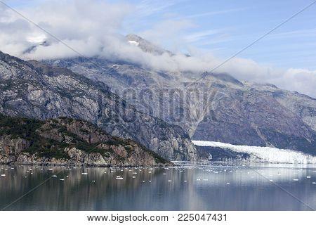 The scenic view of a glacier and a mountainous coastline in Glacier Bay national park (Alaska).